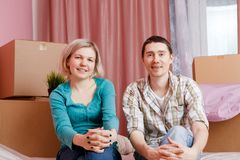 Image of happy men and women sitting on bed among cardboard boxes. In new apartment stock photo