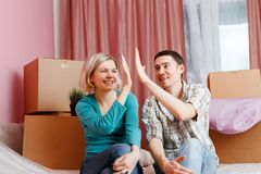 Image of happy men and women sitting on bed among cardboard boxes. In new apartment royalty free stock photography