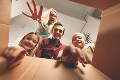 Image of happy parents and children looking inside cardboard box stock image