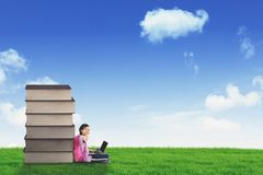 Happy schoolgirl sitting near a pile of books Royalty Free Stock Photos