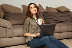 Image of happy slim woman having leisure while sitting on floor Royalty Free Stock Photos