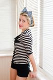 Image of happy smiling pinup girl having fun posing & looking at camera on sun light blinds windows Royalty Free Stock Images