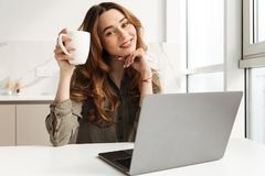 Image of happy woman having leisure while sitting at table in ki Royalty Free Stock Photos