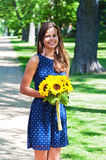 Image of happy woman holding a yellow flowers Royalty Free Stock Image