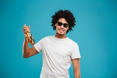 Happy young african curly man holding beer. Image of happy young african curly man standing isolated over blue background holding beer Stock Photography