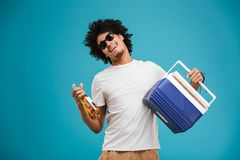 Happy young african curly man holding beer. Image of happy young african curly man standing isolated over blue background holding beer Royalty Free Stock Photo