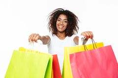 Happy young african woman holding shopping bags. Stock Photo