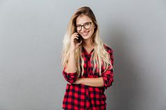 Happy young blonde woman talking by phone. Stock Photos