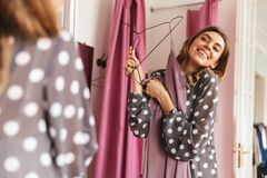 Happy young woman shopaholic looking at mirror. Image of happy young woman shopaholic standing near changing room indoors looking at mirror Stock Photo