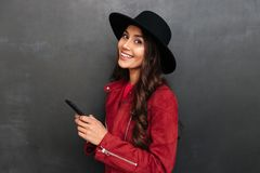Happy young woman wearing hat chatting by mobile phone. Image of happy young woman wearing hat standing over dark grey wall chalkboard chatting by mobile phone Royalty Free Stock Photography