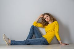 Image of happy young woman wearing yellow shirt and jeans shorts. Over grey background Royalty Free Stock Photography