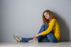 Image of happy young woman wearing yellow shirt and jeans shorts. Over grey background Stock Photo