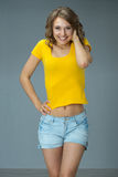 Image of happy young woman wearing yellow shirt and jeans shorts Stock Image