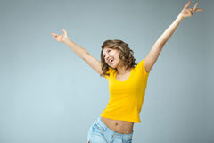 Image of happy young woman wearing yellow shirt and jeans shorts Royalty Free Stock Photography