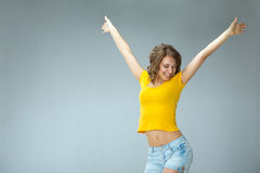 Image of happy young woman wearing yellow shirt and jeans shorts Royalty Free Stock Photo