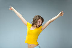 Image of happy young woman wearing yellow shirt and jeans shorts. Over grey background Stock Photos
