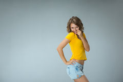 Image of happy young woman wearing yellow shirt and jeans shorts Royalty Free Stock Image