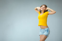Image of happy young woman wearing yellow shirt and jeans shorts Royalty Free Stock Images