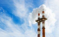 Image haute étroite de deux cheminées d'évacuation des fumées soulevant la fumée photo stock