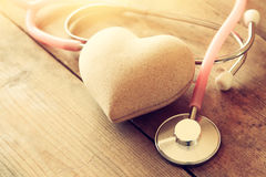 Image of heart and stethoscope. Medical concept. Image of heart and stethoscope on wooden background. Medical concept. Filtered and toned royalty free stock image