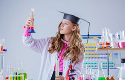 Image of high school girl looking at test tube stock photo
