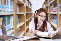 High school student girl reading a book. Image of a high school student girl reading a book while sitting in the library Royalty Free Stock Photography