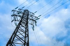 High voltage electricity pylon against cloud. Image of high voltage power line, electricity pylon and blue sky Stock Photo