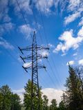 Image of high voltage power line and sky. High-voltage electric pylons and power lines against the blue sky and green trees Stock Photo