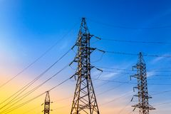 Image of high voltage power line and sky. High voltage electricity pylons and transmission power lines on the blue sky and the sunset sunshine. background Stock Photos