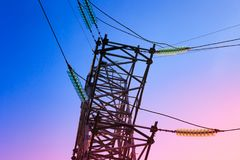 High voltage electricity pylons and transmission power lines on the blue sky background. Royalty Free Stock Photo