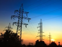Image of high voltage power line and sky. High voltage electricity pylons and transmission power lines on the sunset sky background Stock Photography