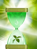 Image of hourglass and plants on  water background Royalty Free Stock Photo