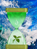 Image of hourglass and plants on  water background Stock Photos