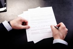 Image of human hand with pen over documents at Royalty Free Stock Photography