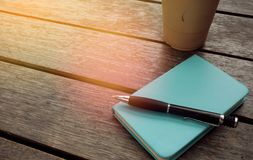 Ice coffee in takeaway cup with notebook and pen on the side. Bo royalty free stock photography