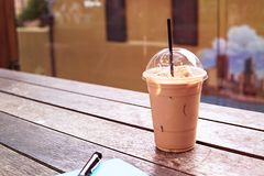 Ice coffee in takeaway cup with notebook and pen on the side. Bo stock image