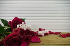 Romantic winter season photography image with marshmallows shaped as snowman with smiles iced on lying in red rose petals Royalty Free Stock Photos