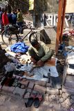 Indian Shoe Repair and Polish Man. An image of a Indian street workers show shop on the side of the road stitching and gluing sandals shoes and high heels stock photos