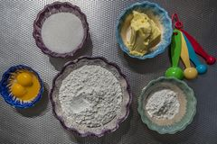 Image of the ingredients to make cookies, cornstarch, sugar, eggs, cornstarch, butter and measuring spoon spoons. That are on a surface of metal, delicious royalty free stock image
