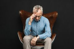 Image of intelligent gentleman 50s having grey hair and beard in. Glasses sitting on businesslike armchair with face downward isolated over black background Royalty Free Stock Image