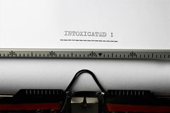 An Image of `intoxicated` written on a typewriter - Close up. Abstract Stock Images