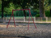Image of red swing in playground stock photo