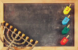 Image of jewish holiday Hanukkah with menorah (traditional Candelabra) and wooden colorful dreidels (spinning top) over chalkboard. Background stock image