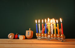 low key image of jewish holiday Hanukkah with menorah (traditional Candelabra) and wooden dreidels spinning top over chalkboard Royalty Free Stock Images