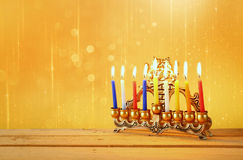 Image of jewish holiday Hanukkah background with menorah (traditional candelabra) and Burning candles with glitter overlay   Royalty Free Stock Image