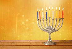 Image of jewish holiday Hanukkah background with menorah (traditional candelabra) and Burning candles with glitter overlay Royalty Free Stock Images
