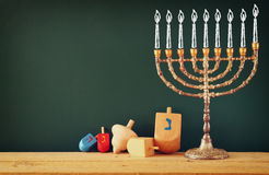 Image of jewish holiday Hanukkah with drawing menorah candles (traditional Candelabra), wooden dreidels (spinning top)  Royalty Free Stock Photo