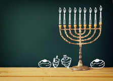 image of jewish holiday Hanukkah with drawing menorah candles (traditional Candelabra), donuts and dreidels (spinning top) Stock Photography