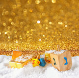 Image of jewish holiday Hanukkah with wooden colorful dreidels (spinning top) and chocolate traditional coins over december snow. Glitter background