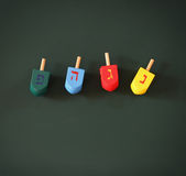 Image of jewish holiday Hanukkah with wooden colorful dreidels (spinning top) over chalkboard background Stock Photo